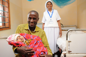 Sister-Yusta-Kiria-of-Charlotte-Health-Centre-in-the-background,-Mr-Musa-Paulo-and-baby-Angela-suffering-from-Pneumonia