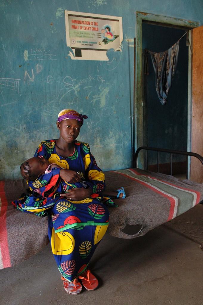 Moeder met ziek kind in het volledig uitgeleefde Maternity Center te Shonga, Kwara State, Nigeria. Als alle 75000 bewoners van Shonga hun polis van het Health Insurance Fund hebben ontvangen, hoeven zij niet langer naar slechte klinieken als deze. (foto Philip Kuypers)